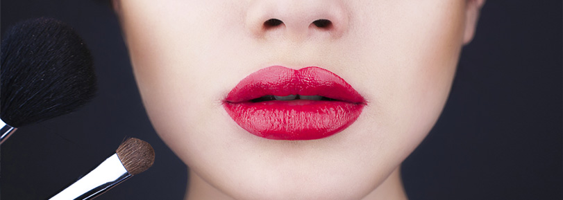 Close up of lips with red lipstick on and make up brushes.