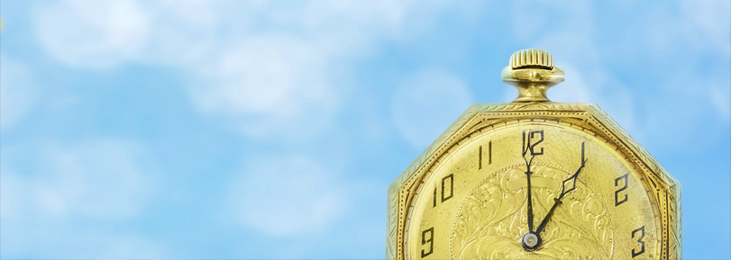 A golden clock on a blue sky background.