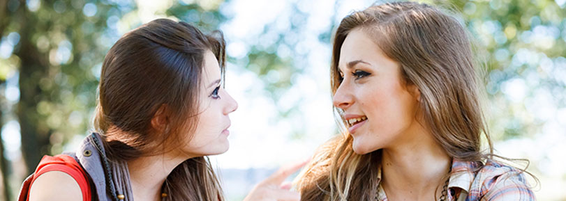 Two young girls talking and listening to each other.