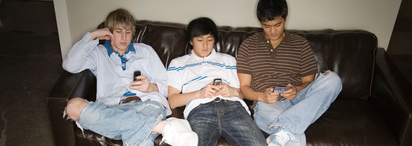 Three teenage boys sitting on a couch, all on their cell phones.